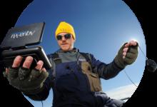 мужчина с камерой для зимней рыбалки в руках