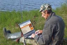 рыбак на берегу с ноутбуком
