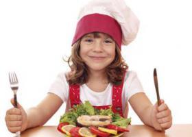 ребенок в поварском колпаке с ножом и вилкой  перед блюдом с рыбой
