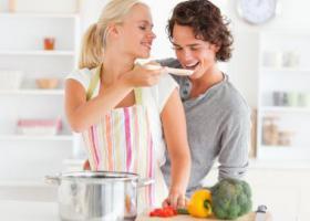 девушка с парнем пробуют суп из кастрюли