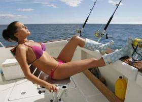 девушка в купальнике на лодке ловит троллингом рыбу