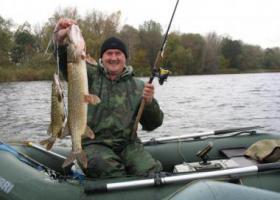 рыбак с большой щукой в надувной лодке